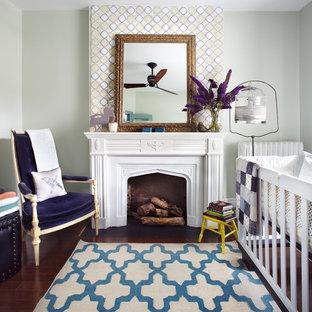 Modelo de habitación de bebé neutra clásica renovada, de tamaño medio, con paredes grises y suelo de madera oscura