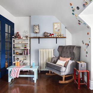 Diseño de habitación de bebé neutra tradicional renovada con paredes azules y suelo de madera oscura