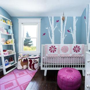 Modelo de habitación de bebé neutra clásica renovada, de tamaño medio, con paredes azules, suelo de madera oscura y suelo marrón