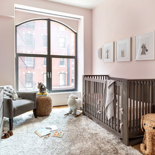 Nursery - mid-sized contemporary girl light wood floor and beige floor nursery idea in New York with pink walls