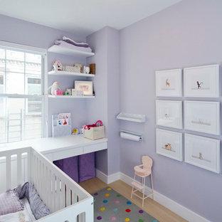 Ejemplo de habitación de bebé neutra nórdica, pequeña, con paredes púrpuras y suelo de madera clara