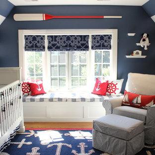 Modelo de habitación de bebé niño costera, pequeña, con paredes azules y suelo de madera en tonos medios