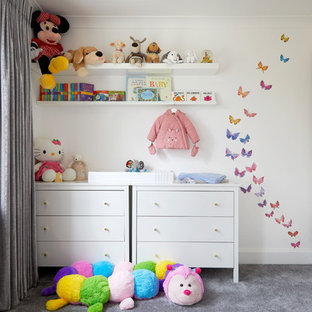 Medium sized contemporary nursery for girls in Kent with carpet, grey floors and white walls.