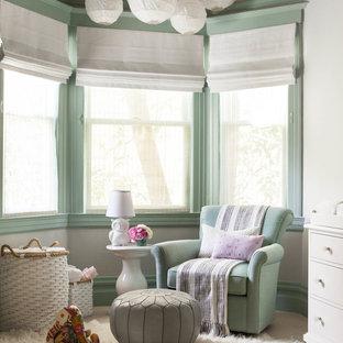 Immagine di una cameretta per neonati neutra classica con pareti verdi e moquette