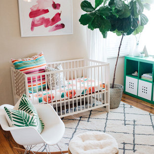 Inspiration for a medium sized bohemian nursery for girls in Orange County with beige walls and medium hardwood flooring.