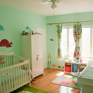 Photo of an expansive contemporary gender neutral nursery in Other with blue walls.