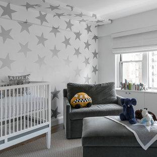 Medium sized contemporary gender neutral nursery in New York with multi-coloured walls, medium hardwood flooring and grey floors.