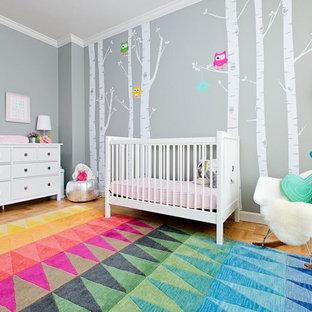 Imagen de habitación de bebé niña actual, de tamaño medio, con paredes grises, suelo multicolor y suelo de madera clara