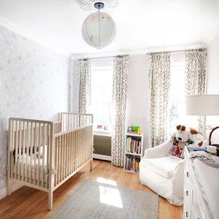 Ejemplo de habitación de bebé neutra clásica renovada, de tamaño medio, con paredes grises, suelo de madera en tonos medios y suelo beige