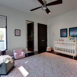 Foto de habitación de bebé neutra actual, grande, con paredes blancas y suelo de madera oscura