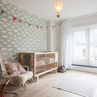 Design ideas for a scandinavian nursery for girls in Amsterdam with white walls, light hardwood flooring and beige floors.