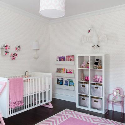 Trendy girl dark wood floor nursery photo in New York with white walls