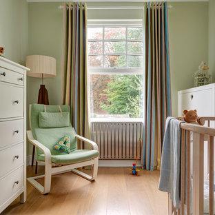 Réalisation d'une chambre de bébé neutre victorienne de taille moyenne avec un mur vert et un sol en bois clair.