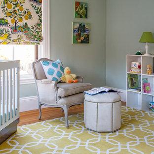 Modelo de habitación de bebé neutra clásica renovada, de tamaño medio, con paredes verdes y suelo de madera en tonos medios