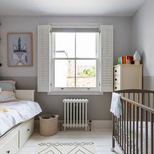 Immagine di una cameretta per neonato scandinava con pareti multicolore, pavimento in legno verniciato e pavimento bianco