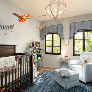 Medium sized mediterranean nursery for boys in Los Angeles with grey walls and light hardwood flooring.