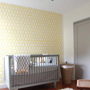 Ejemplo de habitación de bebé neutra actual, pequeña, con paredes amarillas y suelo de madera en tonos medios