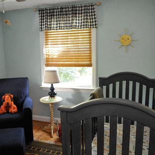 Exemple d'une chambre de bébé garçon chic de taille moyenne avec un mur bleu et un sol en bois clair.