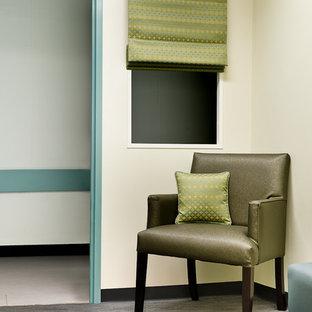 Imagen de habitación de bebé actual con paredes beige y suelo de linóleo