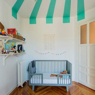 На фото: нейтральная комната для малыша среднего размера в стиле фьюжн с разноцветными стенами, паркетным полом среднего тона и оранжевым полом