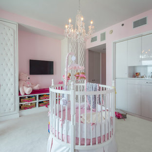 Design ideas for a large traditional nursery for girls in New York with pink walls, carpet and white floors.