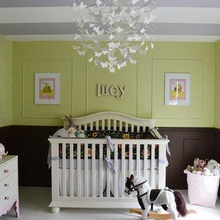 Esempio di una cameretta per neonata tradizionale con pareti verdi e pavimento in legno verniciato