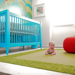 Small modern nursery for boys in Orange County with multi-coloured walls and medium hardwood flooring.