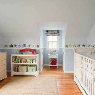 Imagen de habitación de bebé neutra clásica con paredes azules y suelo de madera en tonos medios