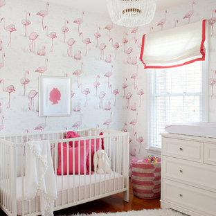 Exemple d'une chambre de bébé fille chic de taille moyenne avec un mur multicolore et un sol en bois brun.