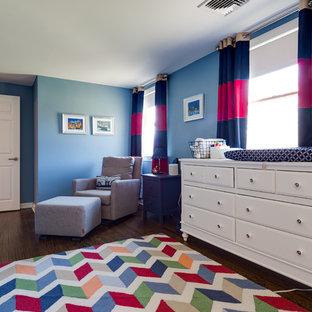 Idée de décoration pour une grand chambre de bébé garçon craftsman avec un mur bleu, un sol en bois foncé et un sol marron.