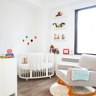 Photo of a small contemporary gender neutral nursery in New York with white walls and medium hardwood flooring.
