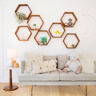 Inspiration for a medium sized modern nursery for girls in Los Angeles with white walls and medium hardwood flooring.
