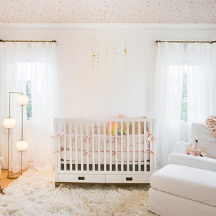 Mid-sized modern nursery in Los Angeles with white walls and medium hardwood floors for girls.