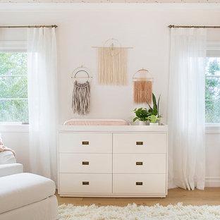 Exemple d'une chambre de bébé fille moderne de taille moyenne avec un mur blanc et un sol en bois brun.