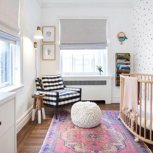Diseño de habitación de bebé niña clásica renovada, pequeña, con paredes blancas, suelo marrón y suelo de madera oscura