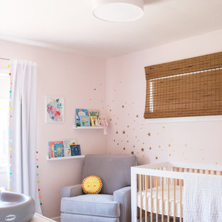 Inspiration for a small bohemian nursery for girls in Los Angeles with pink walls, light hardwood flooring and yellow floors.