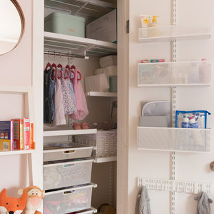 Inspiration for a small eclectic nursery for girls in Los Angeles with pink walls, light hardwood flooring and yellow floors.