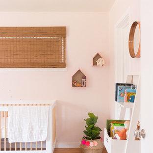 Aménagement d'une petit chambre de bébé fille éclectique avec un mur rose, un sol en bois clair et un sol jaune.