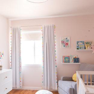 Idées déco pour une petit chambre de bébé fille éclectique avec un mur rose, un sol en bois clair et un sol jaune.