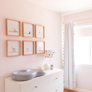 Modelo de habitación de bebé niña bohemia, pequeña, con paredes rosas, suelo de madera clara y suelo amarillo
