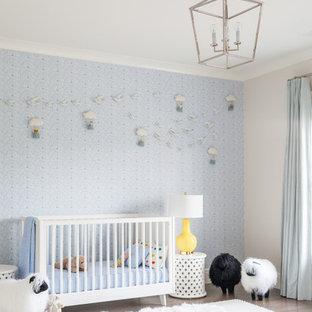 Ejemplo de habitación de bebé niño tradicional renovada, extra grande, con paredes azules y suelo de madera oscura