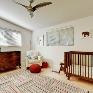 Inspiration for a large midcentury gender-neutral nursery in Austin with white walls, light hardwood floors and beige floor.