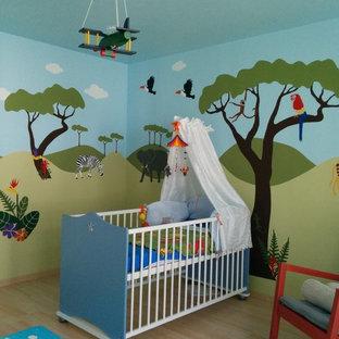 Cette image montre une très grand chambre de bébé neutre design avec un mur bleu.