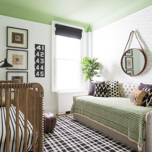 This is an example of a bohemian nursery for boys in DC Metro with green walls and medium hardwood flooring.