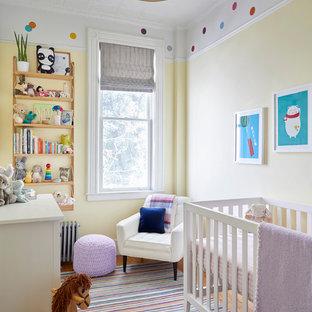 Imagen de habitación de bebé neutra nórdica con paredes amarillas, suelo de madera en tonos medios y suelo beige