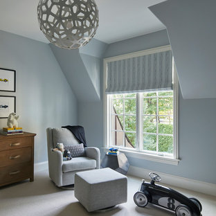 This is an example of a medium sized classic nursery for boys in Chicago with blue walls, carpet and white floors.