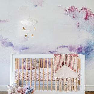 Ejemplo de habitación de bebé niña tradicional renovada, de tamaño medio, con paredes multicolor y suelo de madera en tonos medios