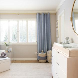 Ejemplo de habitación de bebé niño moderna, grande, con paredes grises y suelo de madera clara