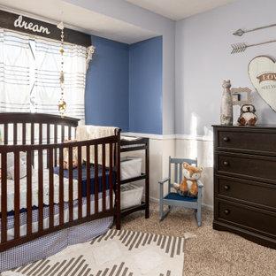Cette image montre une chambre de bébé garçon traditionnelle de taille moyenne avec un mur bleu, moquette, un sol beige et boiseries.
