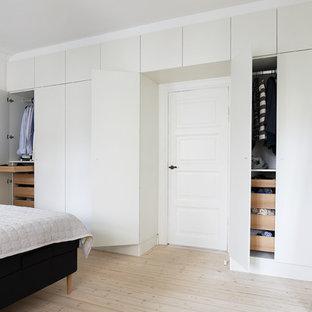 Modelo de armario unisex, nórdico, con armarios con paneles lisos, puertas de armario blancas y suelo de madera clara